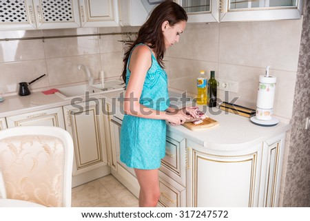 Three Quarter Shot of a Young Woman Slicing Raw Meat to Cook for Lunch at the Home Kitchen. - stock photo