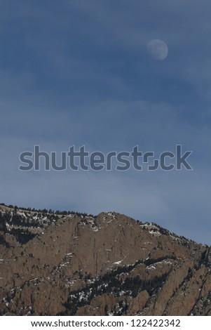 Three-quarters moon over the high cliffs of the Sandia Mountains, near Albuquerque, NM - stock photo