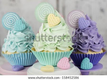 Three rainbow cupcakes with candy - stock photo