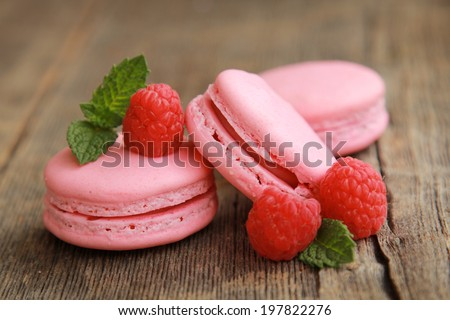 Three raspberry macarons on a wooden table with fresh fruits and mint - stock photo