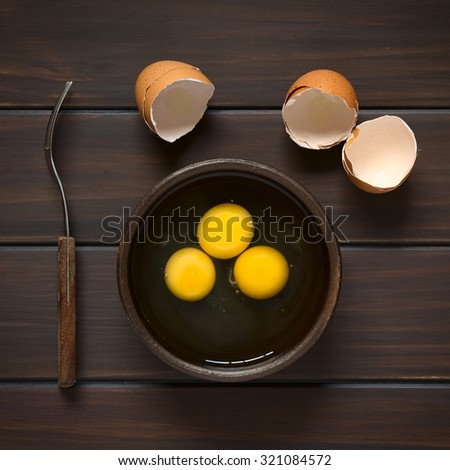Three raw eggs in rustic bowl with fork on the side and broken eggshells above, photographed overhead on dark wood with natural light - stock photo
