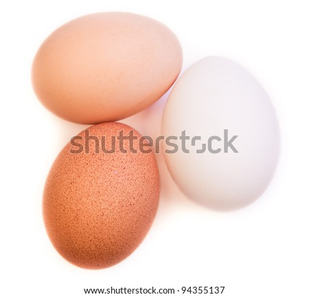 Three raw eggs of different color and variety laying next to each other on a white background with a slight shadow.