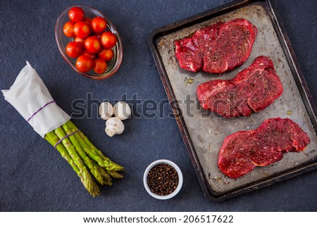 Three raw fillet steaks with green asparagus, mushrooms, cherry tomatoes with a slate background - stock photo
