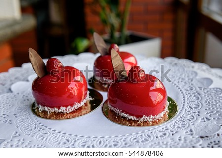 Three red cakes in form of hearts with raspberries on top stand on lace tablecloth