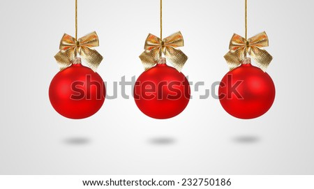 Three red Christmas balls with golden bows isolated on white background
