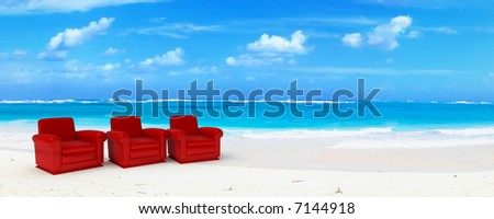 Three red club sofas in an idyillic beach of white sand and blue water