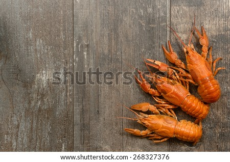 Three red crayfishes in the left-bottom corner on old dark wooden table - stock photo