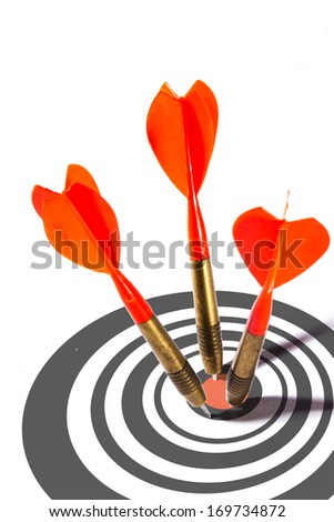 Three red darts in a dart board penetrating the central bulls eye conceptual of precision, aim, accuracy, targets and achievement - stock photo