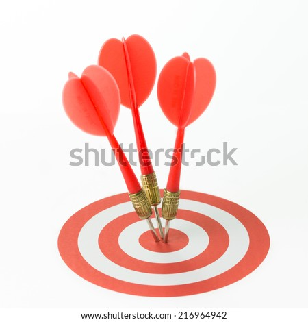 Three red darts pinned right on the center of target - stock photo