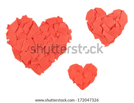Three red heart shapes of torn paper pieces isolated on white - stock photo