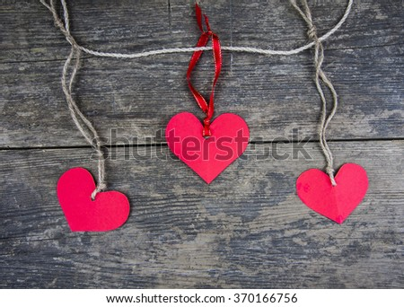 Three red paper hearts connected with a rope on a wooden background - stock photo