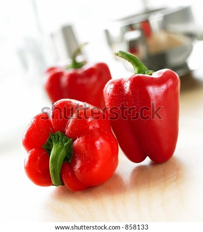Three Red Peppers in the Kitchen - stock photo