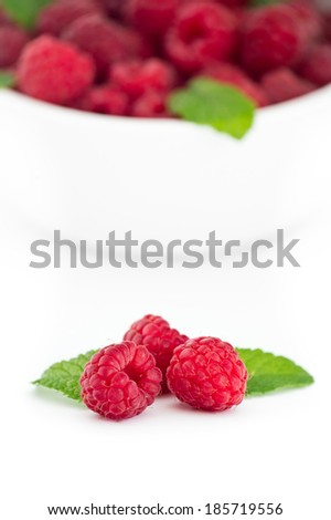 Three red raspberries with fresh mint leaves in front of white bowl with raspberries - stock photo
