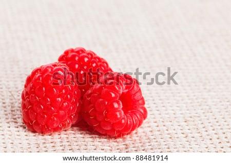 Three red ripe raspberry fruit, on gray linen table cloth, macro - stock photo