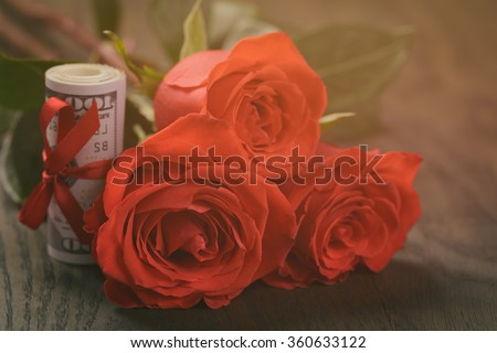 three red roses and bunch of dollars - stock photo