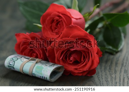 three red roses and bunch of russian money - stock photo