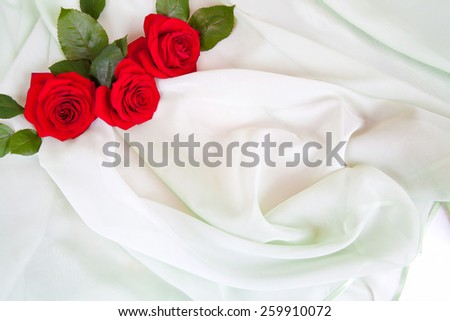 Three red roses lie on the soft green fabric