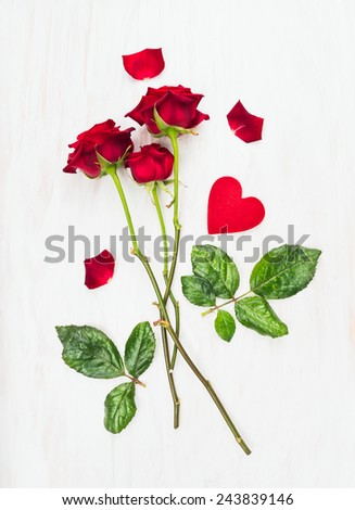 three red roses on long stems and heart on white wood, love card - stock photo