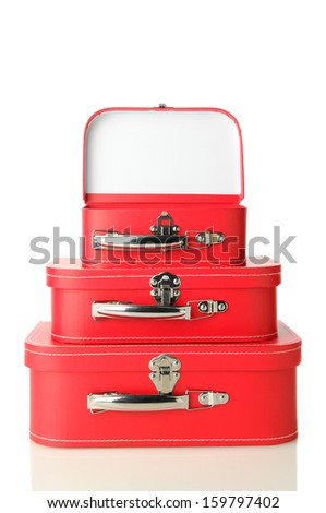 Three red suitcases stacked on a white background with slight reflection. Top bag is open. Vertical format. - stock photo