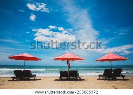 Three red sun umbrellas stay on yellow sand beach with blue sea and blue sky on background. Concept for rest, relaxation, holidays, spa, resort.  - stock photo