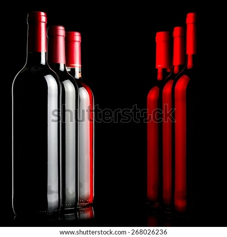 Three red wine bottles with red reflections - stock photo