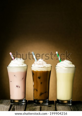 Three refreshing creamy milkshakes in berry, chocolate and lemon flavors topped with a twirl of ice cream or frozen yoghurt on a wooden table against a brown background with copyspace - stock photo