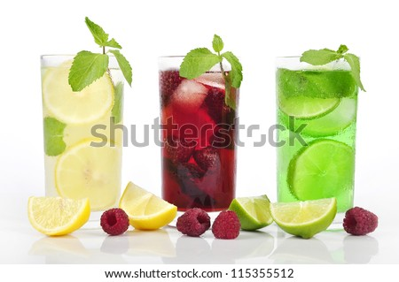 Three refreshing drinks in glasses with mint and ice isolated - stock photo