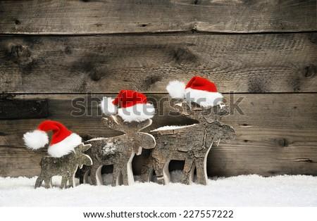 Three reindeer wearing santa hats on brown wooden background. - stock photo