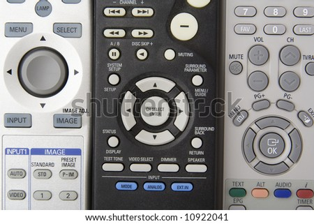 Three remote controls with circular buttons - stock photo
