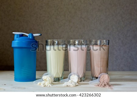 Three resh milk, chocolate, blueberry and banana drinks on table near protein shaker - stock photo