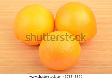 Three ripe orange fruit on wooden background - stock photo