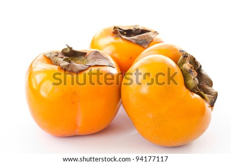 three ripe orange persimmons on a white background - stock photo
