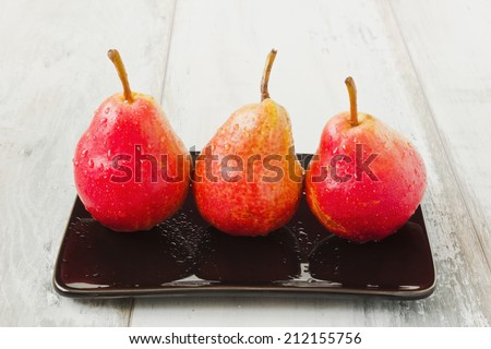 three ripe tasty pears in a black plate on the table.health and diet food - stock photo
