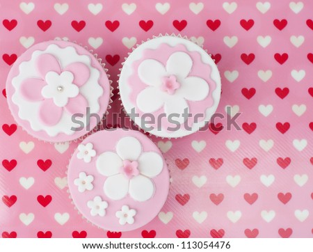 Three romantic flower cupcakes on a pink hearted Valentine background - stock photo