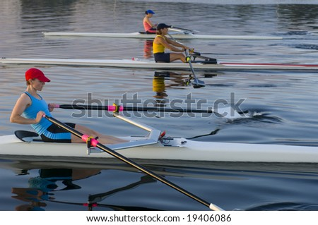 three rowers competing. - stock photo