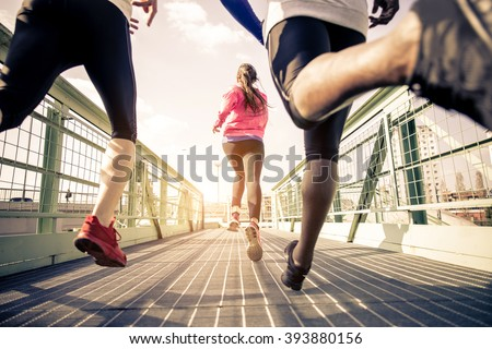 Three runners sprinting outdoors - Sportive people training in a urban area, healthy lifestyle and sport concepts - stock photo