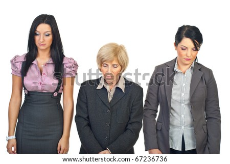 Three sad business women standing in a row and looking down isolated on white background