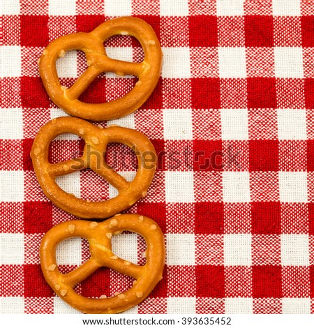 Three salted pretzels on the red white checkered tablecloth background - stock photo