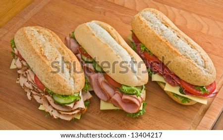 Three sandwiches - roasted turkey breast with cheese, cucumbers and tomatoes, ham and swiss cheese with tomatoes and salami, swiss cheese and tomatoes on a wooden board - stock photo