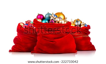 Three Santa Claus red bags with Christmas toys on white background.  - stock photo