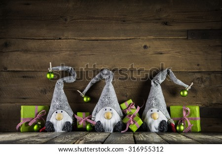 Three santa with red felt hats and apple green christmas presents on an old wooden background for decoration. - stock photo