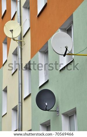 Three satellite dishes on the apartment house - stock photo