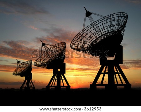 Three satellite dishes over sunset