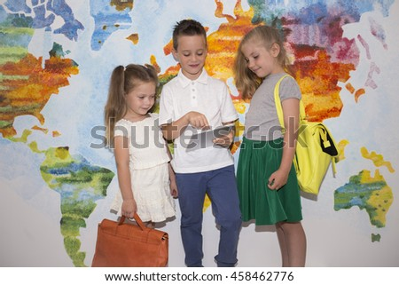 Three school children with a backpack on the background of the world map. Training, education, students, children - stock photo