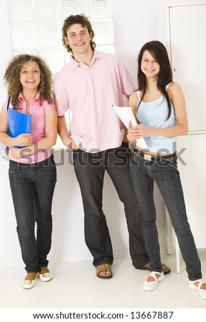Three schoolmate standing near window and talking. Girls holding notebooks. They looking at camera. Front view.