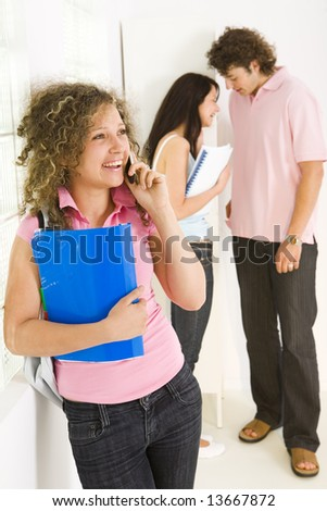 Three schoolmate standing near window. Girls holding notebooks. A boy talking with girl in blue shirt. Girl in pink shirt talking by mobile phone. Focused on girl in pink shirt. - stock photo