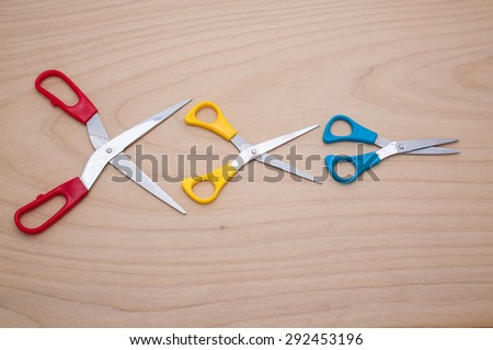 Three scissors like idiom Big fish eat little fish in the business on wooden texture. - stock photo
