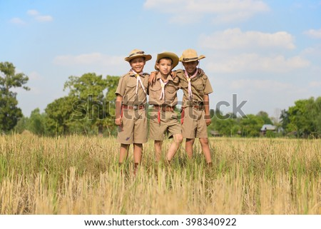 Three scouts stand neck of the field in the camp. - stock photo