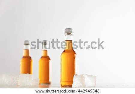 Three sealed bottles with cold cider drink inside isolated on white between ice cubes, presentation mockup - stock photo