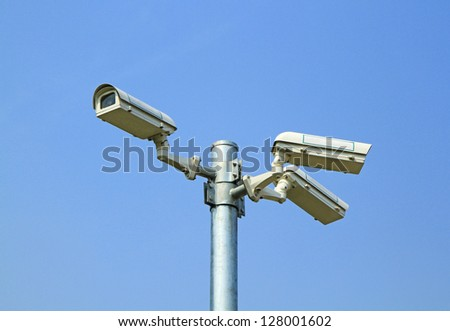 Three security cameras against blue sky - stock photo